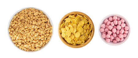Yellow and pink corn cereals for breakfast in round bowls isolated. Pile of crispy corn flakes, cornflakes collection. Cereals set top view