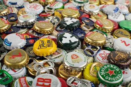 Wroclaw, Poland - April 22, 2019: background with metal caps from different beer bottles of popular Polish beers and international brands such as Tyskie, Okocim, Zywiec, Lech, Heineken etc