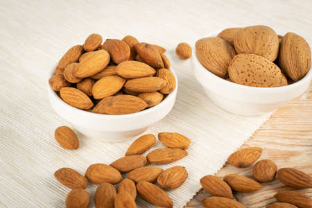 Heap of almond in wooden bowl on rustic background with selective focus. Scattered almonds with shell and peeled nuts closeup Stock Photo