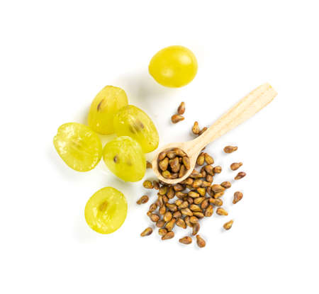 Grape oil seed in small vintage bottle isolated on white background. Heap of grape seeds with green slices and cold press organic essential oil, tincture, extract, infusion 免版税图像