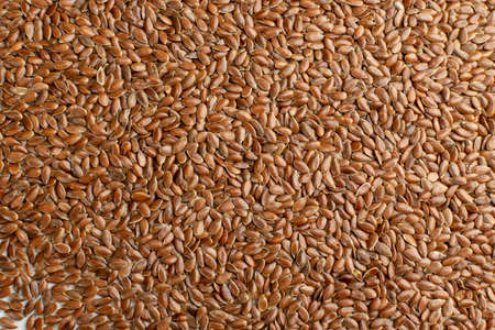 Dry Raw Unpeeled Flax Seeds Texture Background Top View. Uncooked Hulls Linseeds Pattern with Copy Space