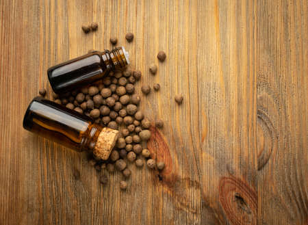 Allspice pepper seeds essential oil in small vintage bottle. Jamaica peppercorns and organic essential oil in medicine jar. Myrtle pepper essence, tincture, extract or infusion mockup Banque d'images