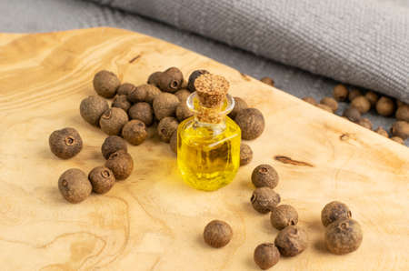 Allspice pepper seeds essential oil in small vintage bottle. Jamaica peppercorns and organic essential oil in medicine jar. Myrtle pepper essence, tincture, extract or infusion mockup