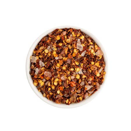 Red chilli pepper flakes with seeds isolated. Pile of broken crushed hot red pepper, dried chili flake with pink salt pieces top view