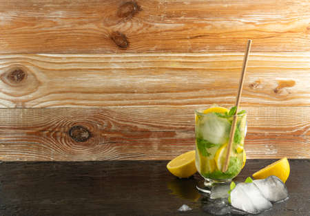 Summer mint lemonade with ice cubes and fresh lemon. Infused lemon water mockup