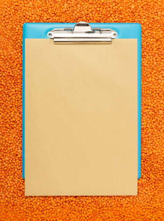 Red lentils texture background with copy space for text. Dry orange lentil grains mockup, dal pattern, raw daal flat lay template top view