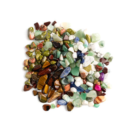 Colorful semiprecious stones mix isolated. Green, red, blue, white, black and purple quartz pebbles top view 免版税图像