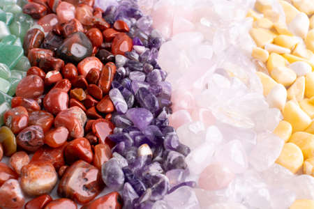 Colorful stones texture background. Green, red, blue, white, black and purple quartz pebbles mix top view