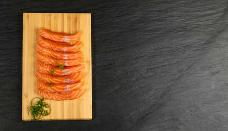Slices of Raw Salmon Fillet on Black Background Mockup Top View. Thick Pieces of Fresh Red Fish or Trout with Copy Space 免版税图像