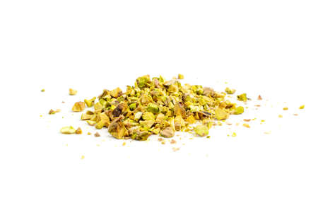 Scattered pistachio nut pieces isolated. Break chopped pistachios pile, fried baked diced pistache on white background Standard-Bild