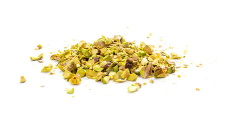 Scattered pistachio nut pieces isolated. Break chopped pistachios pile, fried baked diced pistache on white background