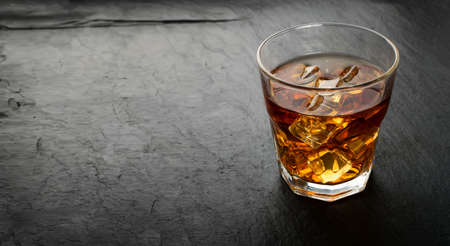 Iced Whiskey Glass on Natural Black Stone Background Close Up. Luxury Bourbon with Ice Cubes, Cold Brandy, Whiskey or Liquor with Place for Text