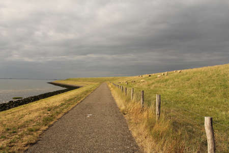 a road under the dike along the western scolds with a stormy sky with clouds in the background