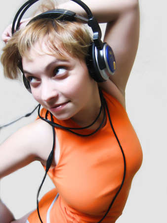 Happy girl with headphones isolated on grey background photo