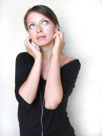 Beautiful girl listening to the music in small headphones Stock Photo - 1379571