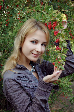Pretty girl touching barberries and smiling photo