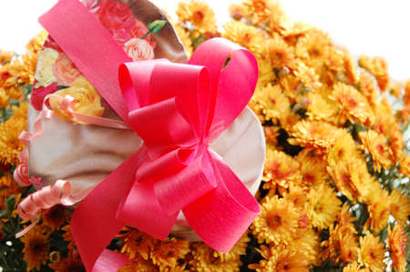 present box with pink ribbon and bouquet of chrysanthemums