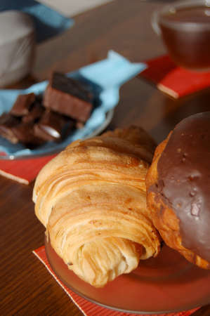 Breakfast with croissant, sweets and a cup of tea photo