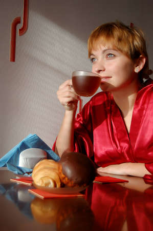 girl having breakfast with cup of tea and croissant photo