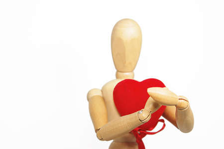 Wooden figurine man holding red fabric heart, focus on hands photo