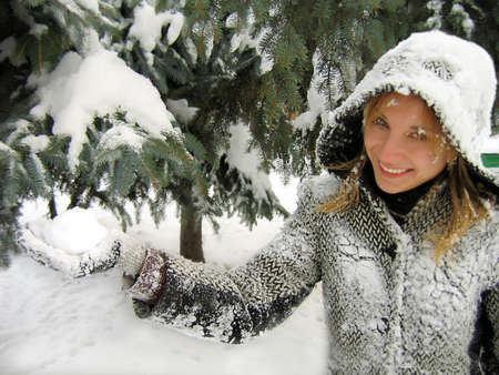 Smiling girl on snowy fir background holding snowball photo