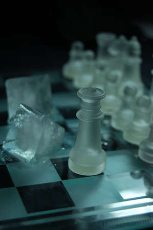 Set of glass chess, queen and ice on board photo