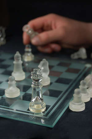 Set of glass chess, hand holding figure photo