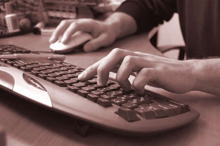 male hand typing on keyboard, red toned Stock Photo