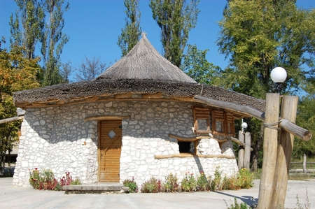 a house with a straw: Small stone house with straw roof Stock Photo