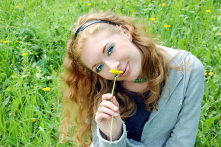 Lovely red-haired girl sniffing dandelion Stock Photo - 2975236
