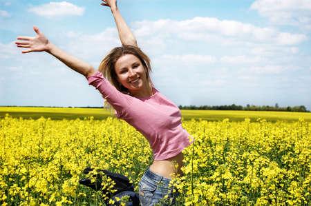 oilseed: Happy girl jumping among rape oilseed field and blue sky