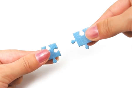 female hands putting together right puzzle isolated