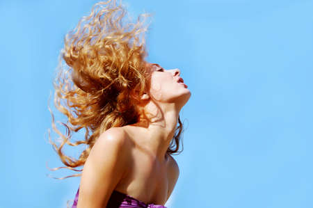 flying hair: beautiful rednead woman with flying hair on blue background Stock Photo