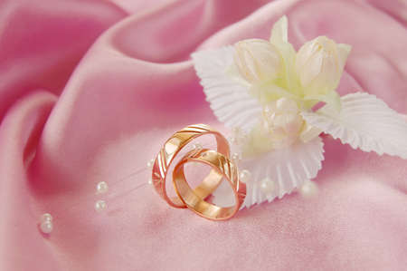 pink satin: wedding golden rings with decoration on pink satin Stock Photo