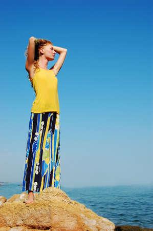 beautiful redhead girl admirinf seashore on rock photo