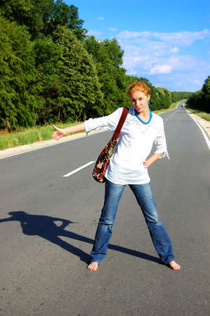 hitchhiking: girl hitchhiking on road under blues sky