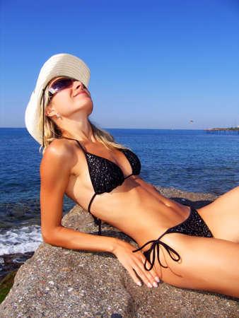 beautiful girl lying on sunny beach with glasses photo