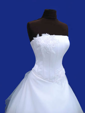 white wedding dress on dummy isolated on blue photo