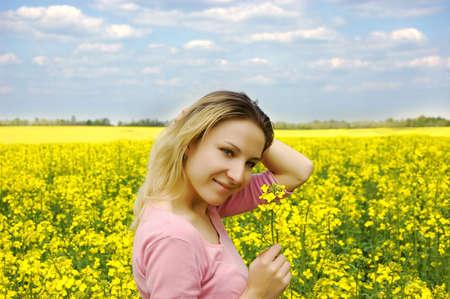 Beautiful girl among blooming rape oilseed field photo