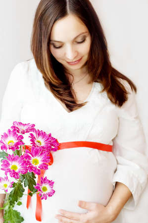 Beautiful pregnant woman holding belly with flowers