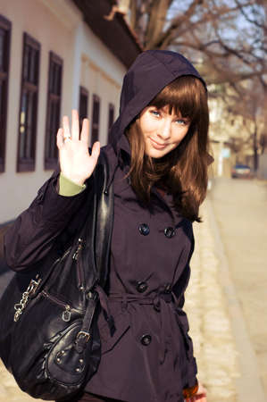 motioning: Beautiful brunette in coat and hood saying hello Stock Photo