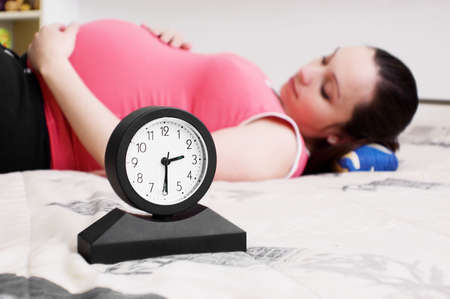 pregnant lying woman and clock, focus on clock Stock Photo