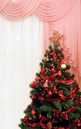 Christmas tree in a room next to window pink curtains photo