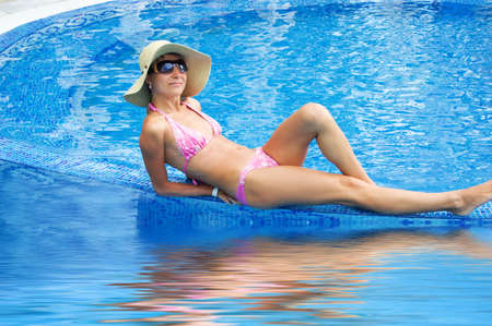 Woman in hat and sunglasses lying in swimming pool with reflection Stock Photo - 5105034