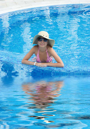 Smiling woman in swimming pool with hat and sunglasses with reflection Stock Photo - 5105035