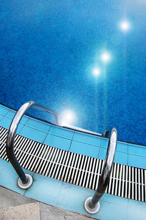 Part of swimming pool with ladder and reflected sun lights