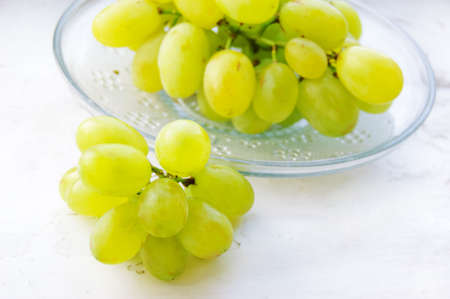 Green ripe grapes in plate on light background Stock Photo - 5430431