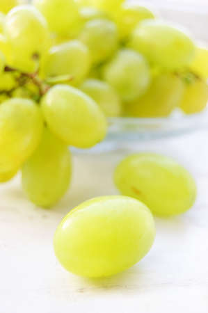 Green ripe grapes in plate on light background Stock Photo - 5430435