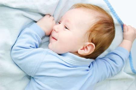 Blue eyed baby boy lying on blanket photo