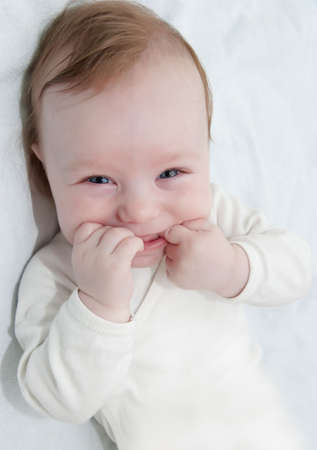 Adorable laughing baby boy lying with hands in his mouth photo